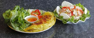 Banh xeo, left, and green mango salad with chicken and shrimp from Pho Binh Minh.