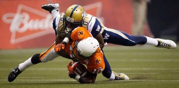 The B.C. Lions' Kierrie Johnson (bottom) is tackled by the Winnipeg Blue Bombers' Johnny Sears after making a reception that was called back due to penalties against both teams during the first half in Vancouver on Friday.