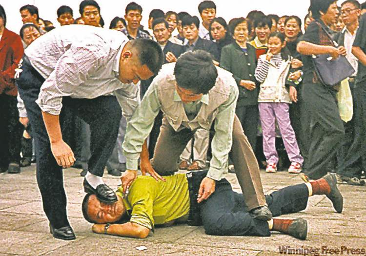 A Falun Gong practitioner is arrested in in Tiananmen Square.