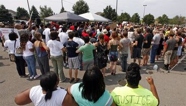 FILE - In this Saturday, Aug. 30, 2014 file photo, demonstrators join arms during a rally outside a Wal-Mart store in Beavercreek, Ohio. The southwest Ohio Wal-Mart store has removed from shelves air rifles like the one a 22-year-old man was holding when he was fatally shot by police Aug. 5. The world's largest retailer says it's a store-specific decision, not a change in national policy. (AP Photo/The Dayton Daily News, Ty Greenlees, File)