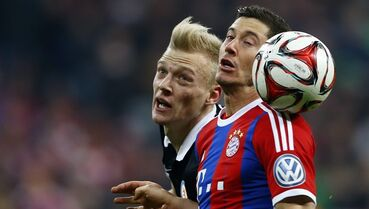 Bayern's Robert Lewandowski, foreground right, and Braunschweig's Saulo Decarli challenge for the ball during the German Soccer Cup round of sixteen match between FC Bayern Munich and Eintracht Braunschweig in Munich, southern Germany, Wednesday, March 4, 2015. (AP Photo/Matthias Schrader)