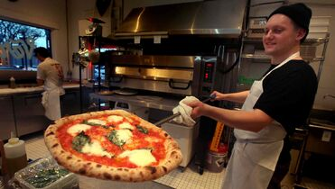 Sean Divids shows off a margherita pizza at the south Osborne Street restaurant.