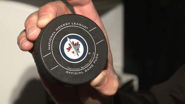 NHL off-ice officials crew supervisor Ron Ottawa holds one of the official game pucks, which is removed from a freezer prior to every game.