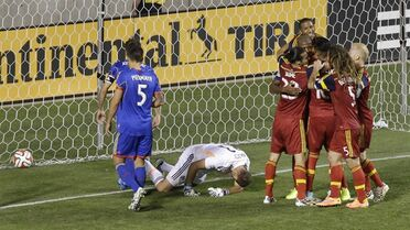Colorado Rapids goalkeeper Joe Nasco (23) falls to the ground as Real Salt Lake players celebrate after Chris Schuler (28) goal in the first half during an MLS soccer game Friday, Sept. 19, 2014, in Sandy, Utah. (AP Photo/Rick Bowmer)