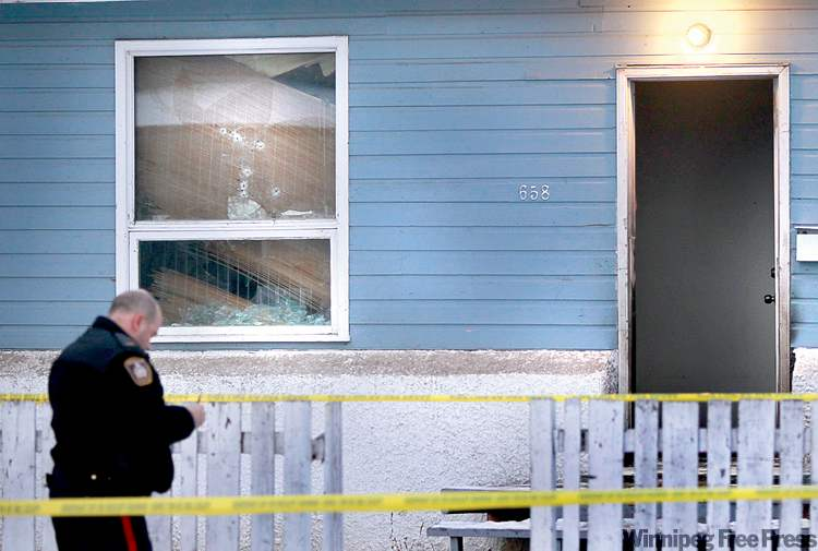 Police investigate after a Victor Street house was shot up and set afire Wednesday.