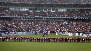 Fans and players stand for the national anthem during the opening ceremonies as the San Francisco Giants take on the Kansas City Royals in Game 3 of the baseball World Series, Friday, Oct. 24, 2014, in San Francisco. (AP Photo/Bay Area News Group, Patrick Tehan)