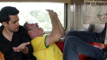 This undated screenshot provided by Snack, a web video company, shows Seth Kugel, right, bothering a fellow rider with his outburst on a New York City subway train as part of a new YouTube video series teaching Brazilian visitors about life in New York. The often hilarious short videos are being promoted to Brazilian travelers and tackle subjects like how to ride the subway and how to eat a bagel. The screenshot illustrates that it's inappropriate to behave so boisterously on a train. (AP Photo/Snack)