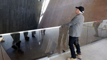 Canadian Museum for Human Rights architect Antoine Predock gets tour of the museum he designed , in picture Predock inspects baslt rock wall seen    from  second level  walkway ascending throughout the museum ,  May 29 2014 / KEN GIGLIOTTI / WINNIPEG FREE PRESS