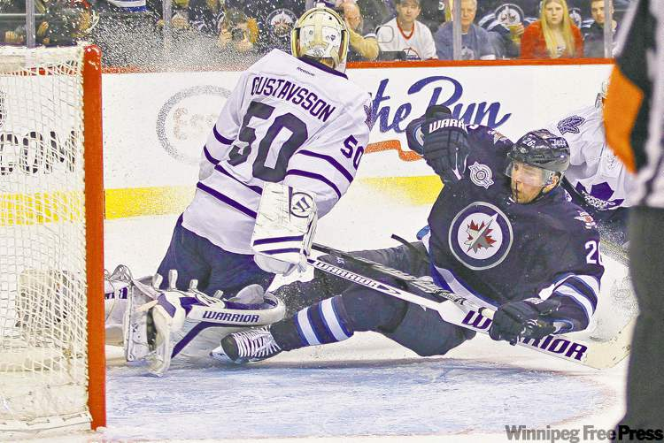Jets forward Blake Wheeler crashes into Toronto Maple Leafs goaltender Jonas Gustavsson during second-period NHL action at the MTS Centre last season. On Saturday the Jets traded to acquire the right to negotiate with Gustavsson.