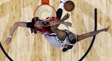 New Orleans Pelicans forward Anthony Davis, top left, and San Antonio Spurs center Boris Diaw (33) battle under the basket in the first half of an NBA basketball game in New Orleans, Wednesday, April 15, 2015. (AP Photo/Gerald Herbert)