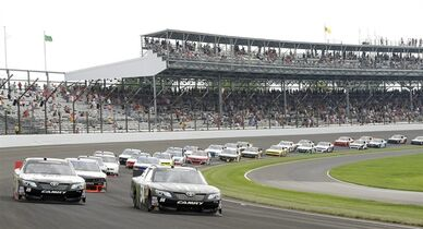 Kyle Busch (54) leads the field out of Turn1 following the start of the Nationwide auto race at Indianapolis Motor Speedway in Indianapolis, Saturday, July 26, 2014. (AP Photo/Darron Cummings)