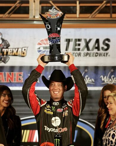 Kyle Busch celebrates in Victory Lane after winning the NASCAR Trucks series auto arce at Texas Motor Speedway on Friday, Oct. 31, 2014, in Fort Worth, Texas. (AP Photo/Fort Worth Star-Telegram, Bob Booth)