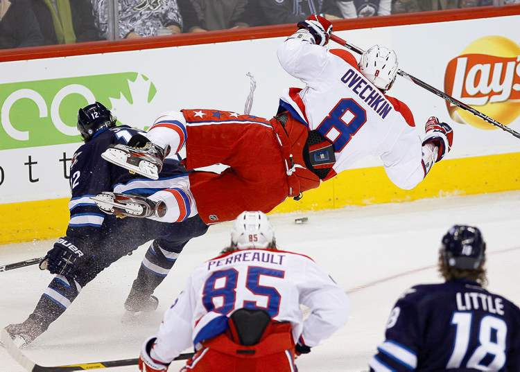 Jets' Randy Jones sends Capitals' Alex Ovechkin flying with a hard check during the first period Friday at the MTS Centre.