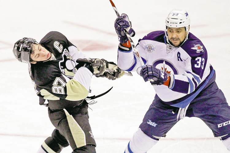 Pittsburgh Penguins' Sidney Crosby gets a high stick from Winnipeg Jets' Dustin Byfuglien in the first period of the teams'  NHL tussle in Pittsburgh Tuesday.