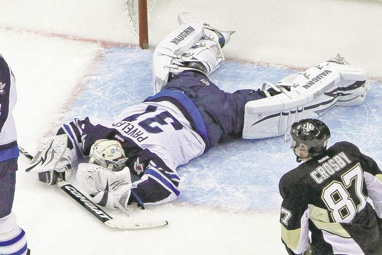 Winnipeg goalie Ondrej Pavelec lies on the ice as Pens captain Sidney Crosby joins the celebration after assisting on teammate James Neal's first-period goal Tuesday.