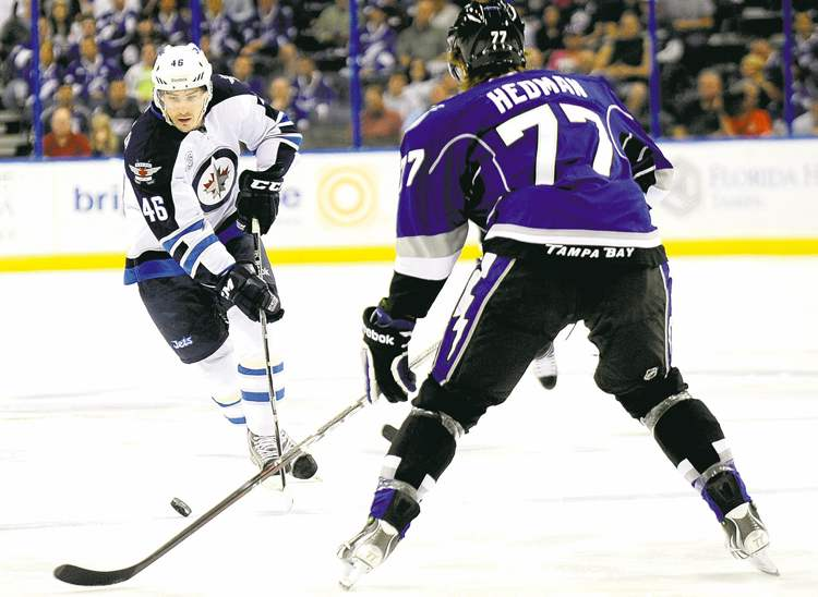 photos by brian blanco / the associated pressJets right wing Spencer Machacek stickhandles against Lightning�s Victor Hedman.