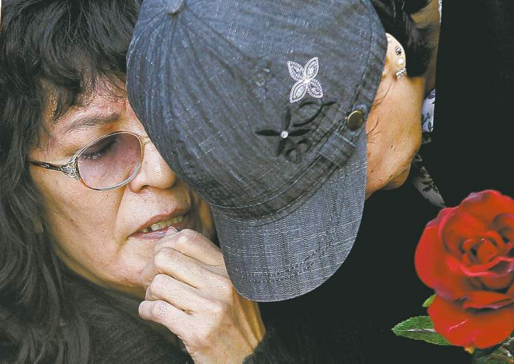 Carolyn Marie Sinclair's mother is comforted at a vigil Tuesday in the lane where her body was found.
