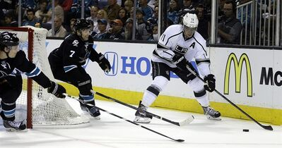 Los Angeles Kings' Anze Kopitar, right, moves the puck past San Jose Sharks' Brad Stuart (7) during the first period of Game 1 of an NHL hockey first-round playoff series Thursday, April 17, 2014, in San Jose, Calif. (AP Photo/Ben Margot)