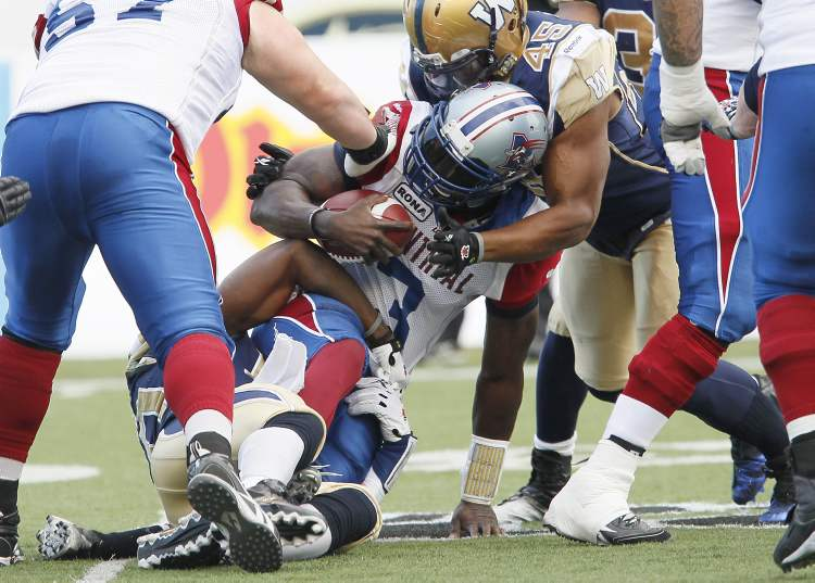 Montreal Alouettes' Adrian McPherson (3) is sacked by Winnipeg Blue Bombers' Henoc Muamba (10) and Rodney Fritz (45) during the first half of their CFL game in Winnipeg Saturday.