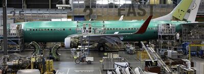 In this photo taken June 3, 2011, An employee rides a trike past a Boeing Co. 737 airplane at the company's assembly facility in Renton, Wash. THE CANADIAN PRESS/AP, Ted S. Warren