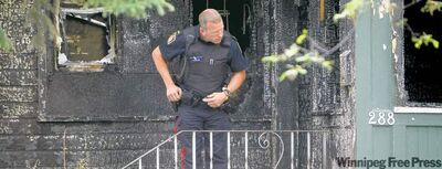 A police officer stands watch at the scene of a house fire on Austin Street North in July that killed five people.
