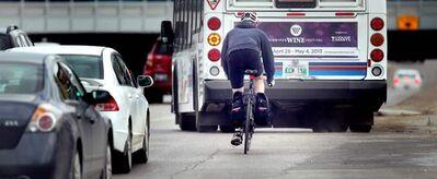A cyclist is surrounded by a lot of heavy metal while navigating through Confusion Corner during rush hour Wednesday afternoon.