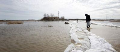 A man attempts to fix a dike at Lake St. Martin on May 6, 2011. Two days later, the community was abandoned.