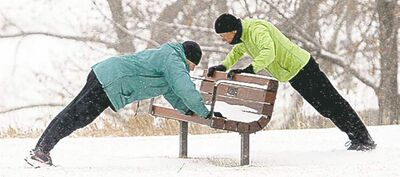 Two women in Calgary do pushups on a park bench.