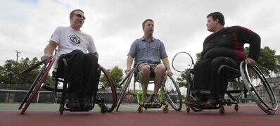 Wheelchair tennis players Jason Betker, left and Sam Unrau explain the fundamentals of wheelchair tennis to Free Press reporter Geoff Kirbyson (centre).