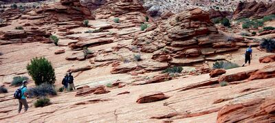 Hikers walk on rocky terrain for a 3-mile trip to The Wave rock formation in the Vermilion Cliffs National Monument. People who make the hike are advised to bring at least a gallon of water for the desert back-country journey that  begins in southern Utah and crosses over the border into Arizona.