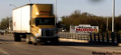 A semi on Tuesday morning goes over a bridge crossing  the Morris River at the north end of  Morris.