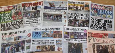 A photograph showing a selection of British and Irish papers for Saturday, Dec. 15, 2012, in London, showing their front page headlines and reaction to the Connecticut School shooting.