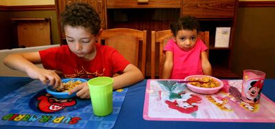 Myrddin Wiltshire, 6, left, digs into his dinner, while his sister Rinoa, 5, looks more reluctant. Myrddin is usually the picky eater, sometimes to the point of tears at the table.