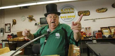 Auctioneer Andy Kaye owner of Kaye's Auction House Inc. on Stanley Street shows some of his auctioneering skills. He is wearing the top hat and glasses he keeps on display.