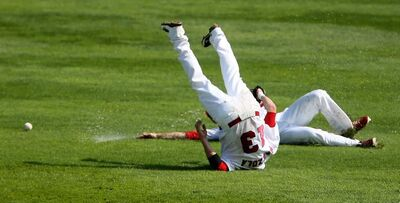 Winnipeg Goldeyes' Josh Mazzola slips while backpedalling and ends up on his head while outfielder Tyler Graham slips behind him while both were trying to catch a fly ball early in a game against the Kansas City T-Bones at Shaw Park on Sunday.