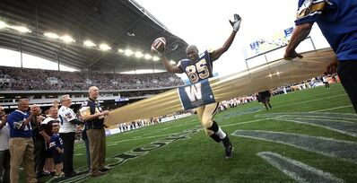 Former Blue Bomber great Milt Stegall runs through a gold ribbon after catching a pass from Matt Dunigan to officially open the Investors Group Field and the CFL regular season Thursday night.
