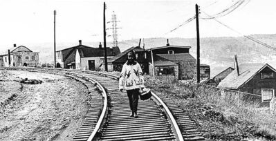The Canadian Press ArchivesA woman walks along the tracks in Africville in Halifax in this undated photo. The settlement was torn down in the 1960s.