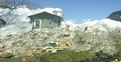 SHELBY WATTS / THE CANADIAN PRESSLumber and other building materials lie scattered after an ice floe wrecked houses on Lake Dauphin�s Ochre Beach Friday.