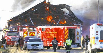 The barn roof starts to collapse in Friday's fire.