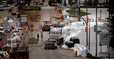 "Giant ""superbags"" keep the swollen Assiniboine River at bay in Brandon's Assiniboine Valley at 18th Street and Kirkcaldy Drive. Traffic has been reduced to two lanes and a neighbouring big-box shopping centre was closed to reduce traffic alongside the dike. The only other major route across the valley, First Street, has been shut down leaving 18th as the only north-south route open."