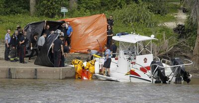 Police and water rescue personnel move a body from the Red River to the riverbank near Waterfront Drive Saturday.