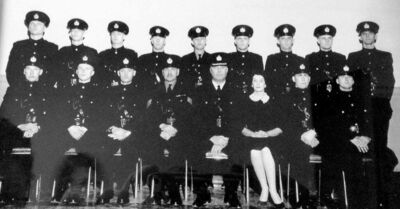Helen Woollard was the first female officer to graduate from a recruit class and be issued a uniform. In this 1960 graduation photo of Winnipeg Police Department class #56, she's in civilian clothes.