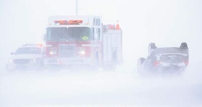 TREVOR HAGAN / WINNIPEG FREE PRESS A vehicle sits on its roof on the North Perimeter Highway near Brookside Boulevard Monday. Blowing snow caused poor visibility throughout southern Manitoba.