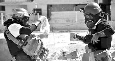 Members of the UN investigation team take samples from sand near a part of a missile suspected to be one of the chemical rockets in the Damascus countryside of Ain Terma, Syria.
