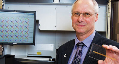 Dr. Jim Davie holds a slide that has been prepared to be analyzed by a gene sequencing machine.