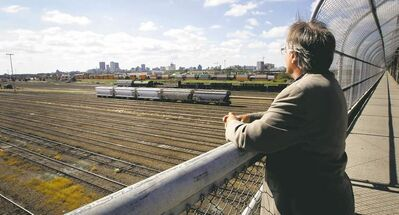 Dennis Lewycky looks out at the CP Rail Yards from the railing on the Arlington Street bridge.