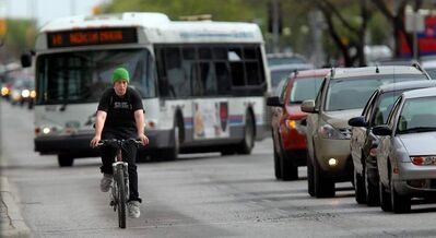 A cyclist rides north on Main street between Pioneer and Portage Avenue  using the bus/bike lane. New bike lanes are being built on Pembina Highway.