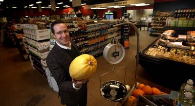 Vita Health's Matt Holtmann shows a melon Tuesday in local health-food chain's newest store at 3500 Portage Avenue.