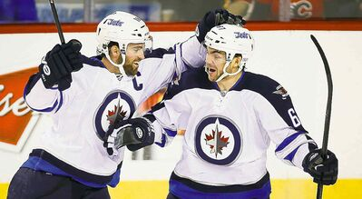 Jeff McIntosh / THE CANADIAN PRESS FILESRight-winger Michael Frolik (right) celebrates a goal with Jets teammate Andrew Ladd in Calgary.