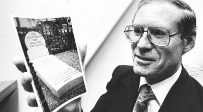 Bert Mayes is shown with a photo of Lord Selkirk's grave in a Free Press file photo.